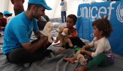 On 13 August 2014, (foreground) a UNICEF staff member and two young girls play with hand puppets from a recreation kit, inside a UNICEF child-friendly tent in the town of Peshkhabour, near the border with the Syrian Arab Republic, in Dohuk Governorate. Other displaced people and UNICEF staff are behind them. UNICEF is providing child protection services and water, hygiene and early childhood development supplies for displaced Yazidi crossing into Kurdistan from the Syrian Arab Republic. The staff member's clothing and other items in the tent bear the UNICEF logo.  In early August 2014 in Iraq, some 1.2 million people have been displaced since the beginning of the year. Recent fighting in Sinjar District, in Ninewa Governorate, displaced nearly 200,000 people, most of whom are members of the ethno-religious Yazidi group. Thousands of families fled to Sinjar Mountain to escape but, instead, became trapped, without access to food or water. Up to 25,000 children were among those stranded. Thousands of people managed to escape into the Syrian Arab Republic before making their way back into Dohuk Governorate, part of Iraq's northern Kurdistan Region. Overall, the region hosts an estimated 700,000 displaced Iraqis, in addition to some 220,000 refugees from the Syrian Arab Republic.